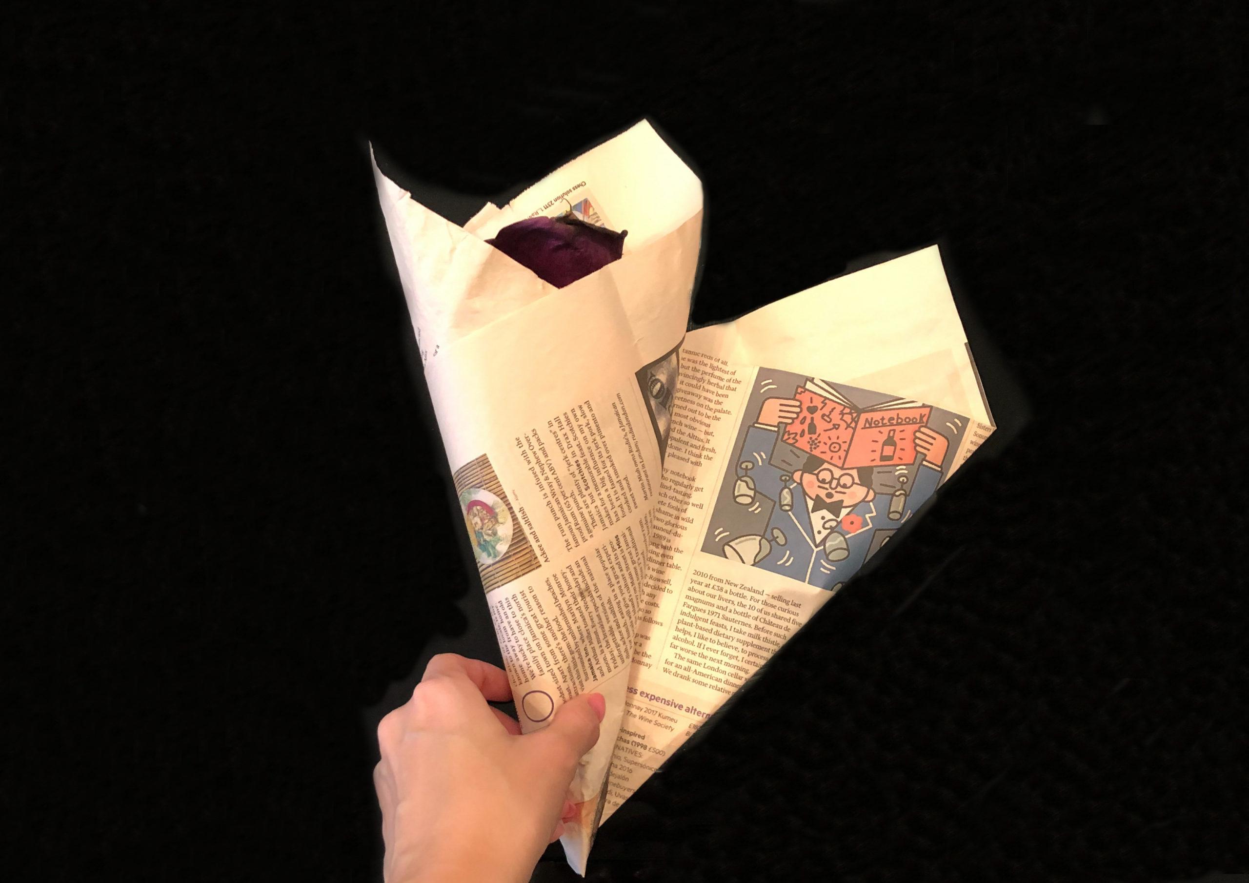 包装紙で枯れた花を包んでいるところを撮影した画像