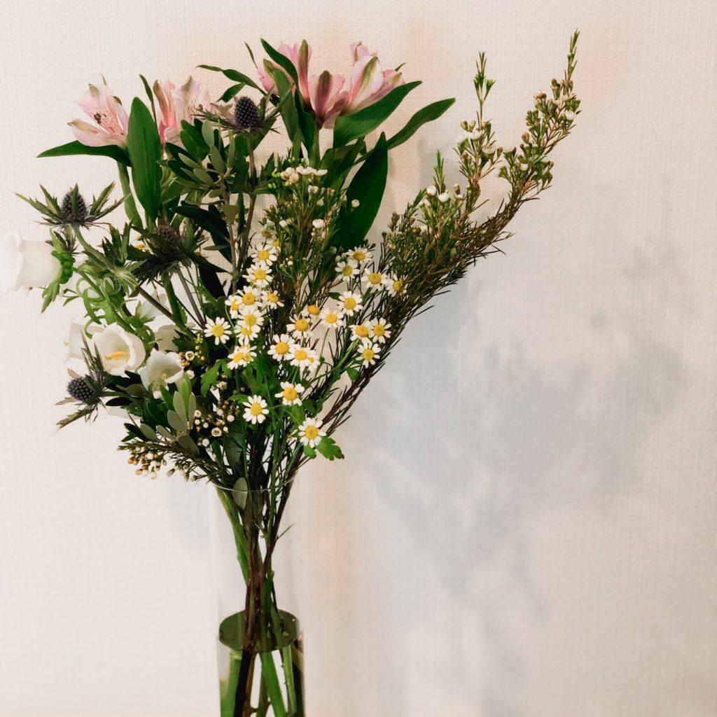 シリンダータイプの花瓶を使って私が作ったマトリカリアとアルストロメリアとエリンジウムのアレンジメントを撮影した写真