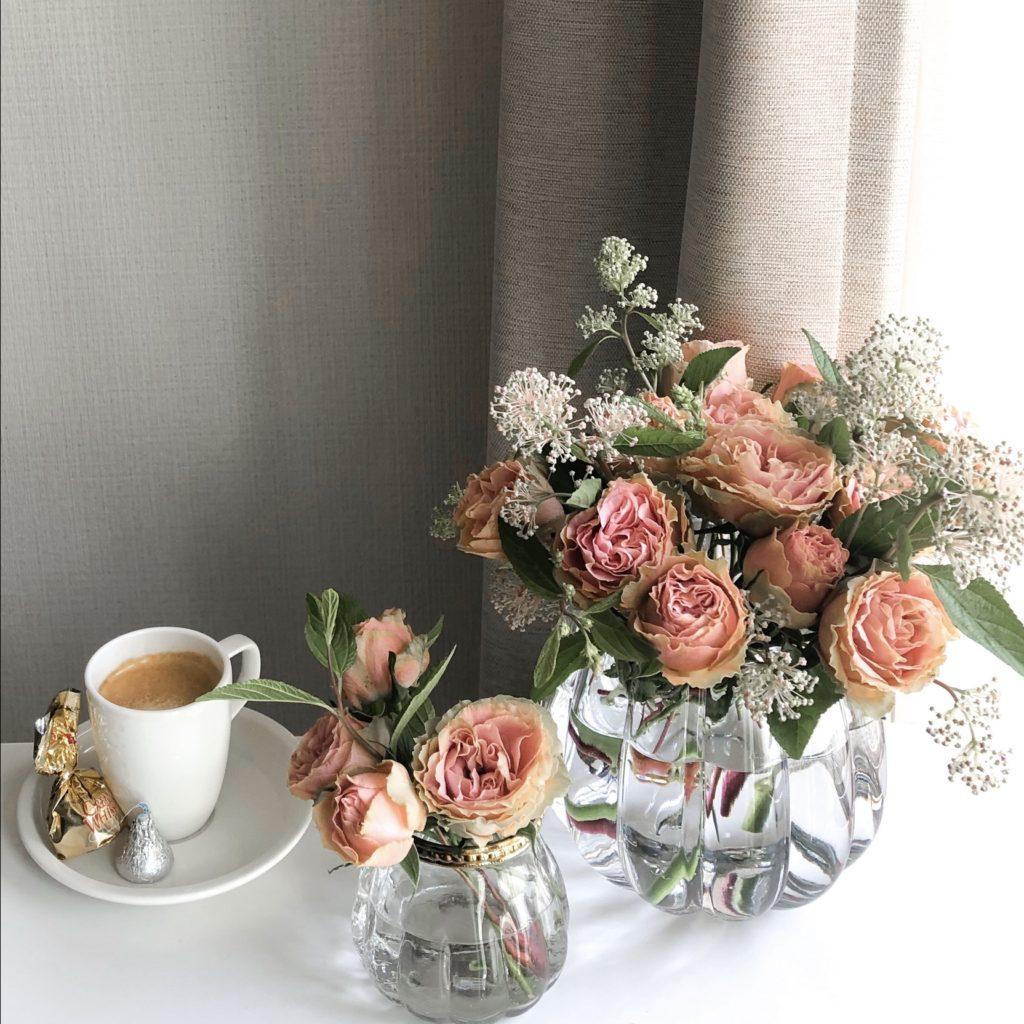 丸型の花瓶を使って私が作ったバラとカリフォルニアライラックのアレンジメントを撮影した写真